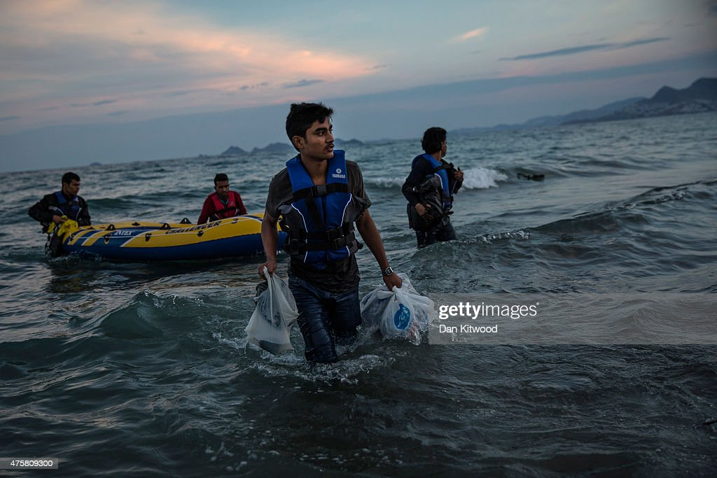 Pakistani migrant men arrive on the beach in a dinghy at dawn after making their way from Turkey on June 04 2015 in Kos Greece Many migrants are...