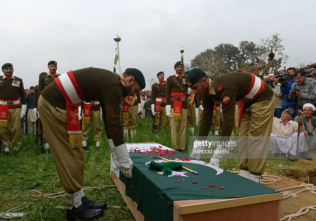 Pakistani military personnel prepare to bury a soldier who was shot dead along the Line of Control (LoC), at a village in Bainso, about 45 kms from the capital Islamabad, on February 16, 2013. Indian troops shot dead a Pakistani soldier along the de facto border in the disputed Kashmir region in the first deadly exchange since a truce was agreed a month ago, officials said Friday. AFP PHOTO/Farooq NAEEM