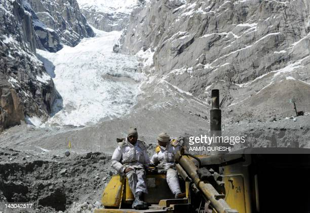 Pakistani military personnel use heavy machinery as they search for avalanche victims during an ongoing operation at Gayari camp near the Siachen...