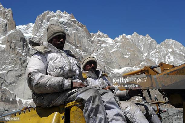 Pakistani military personnel use heavy machinery as they search for avalanche victims during an ongoing operation at the Gayari camp near the Siachen...