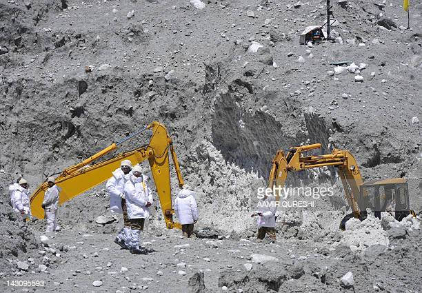 Pakistani military personnell use heavy machinery as they search for avalanche victims during an ongoing operation at Gayari camp near the Siachen...