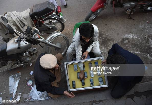 A Pakistani mobile vendor deals with customers at his roadside stall in Rawalpindi on January 6 2015 Latest statistics issued by Pakistan...