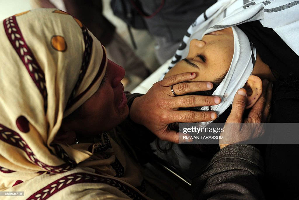 A Pakistani mother mourns over her daughter, who was killed while on the job as a polio vaccination worker, at a hospital morgue following an attack by gunmen in Karachi on December 18, 2012. Gunmen on motorbikes shot dead five female Pakistani polio vaccination workers on Tuesday, police said, highlighting resistance to the country's immunisation campaign. Four were killed in three different incidents in the sprawling port city and the fifth in the northwestern city of Peshawar, on the second day of a nationwide three-day drive against the disease, which is endemic in Pakistan. AFP PHOTO/Rizwan TABASSUM