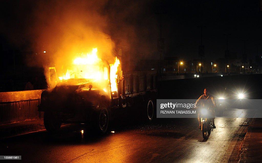Pakistani motorcyclists ride past a burning truck torched by an angry mob following sectarian killing in Karachi on November 6, 2012. Gunmen shot dead three Shiite Muslims and wounded two others on Tuesday in a fresh sectarian attack in Pakistan's troubled southwestern province of Baluchistan, police said. AFP PHOTO / RIZWAN TABASSUM