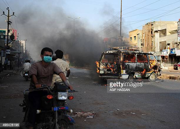 Pakistani motorcyclists ride past a burning vehicle on a street in Karachi on June 3 2014 following the arrest of Altaf Hussain head of Pakistan's...