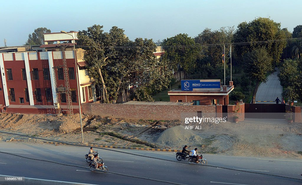 Pakistani motorcyclists ride past a sealed medicine factory in Lahore on November 26, 2012. At least 16 people have died after drinking a toxic cough syrup in the Pakistani city of Lahore, forcing authorities to close three pharmacies and a medicine factory, officials said. AFP PHOTO/Arif ALI