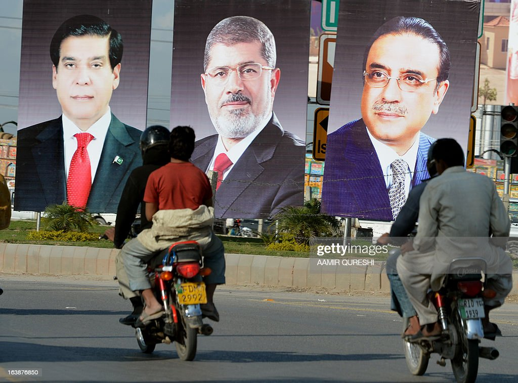 Pakistani motorcyclists ride past billboards featuring photographs of Egyptian President Mohamed Morsi, (C), Pakistani President Asif Ali Zardari (R) and Prime Minister Raja Pervez Ashraf along a street in Islamabad on March 17, 2013. Morsi will visit Pakistan this week on a one-day state visit, Pakistan's Foreign Ministry said. Morsi is due in the country on March 18 by invitation of President Asif Ali Zardari and will bring with him 'a high-powered delegation', according to a ministry spokesman.
