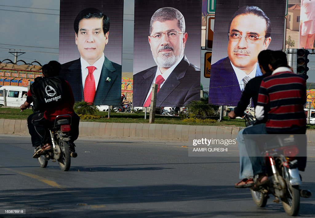 Pakistani motorcyclists ride past billboards featuring portraits of Egyptian President Mohamed Morsi (C), Pakistani President Asif Ali Zardari (R) and Prime Minister Raja Pervez Ashraf along a street in Islamabad on March 17, 2013. Morsi will visit Pakistan this week on a one-day state visit, Pakistan's Foreign Ministry said. Morsi is due in the country on March 18 by invitation of President Asif Ali Zardari and will bring with him 'a high-powered delegation', according to a ministry spokesman. AFP PHOTO/ AAMIR QURESHI