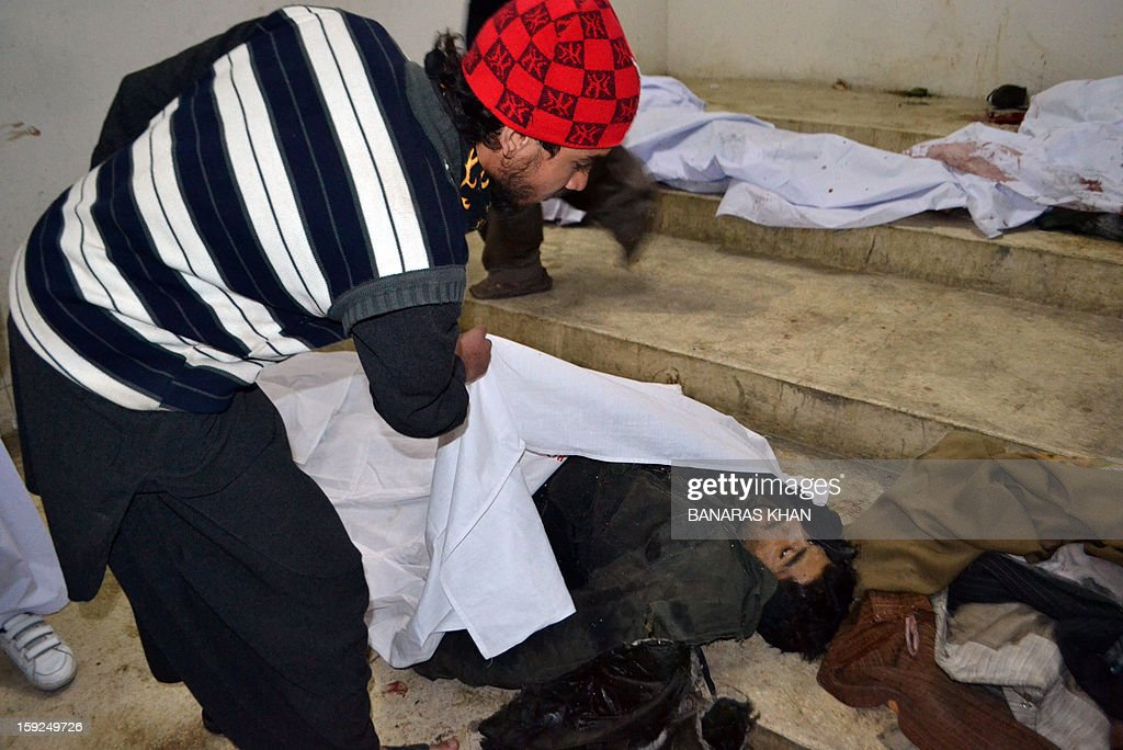 A Pakistani mourner tries to identify a body at a hospital following a bomb attack in Quetta on January 10, 2013. At least 57 people were killed in the southwestern city of Quetta as two successive bombs exploded, with one bomb blast occurring outside a snooker club hours after another blast had already left many casualties, police said.