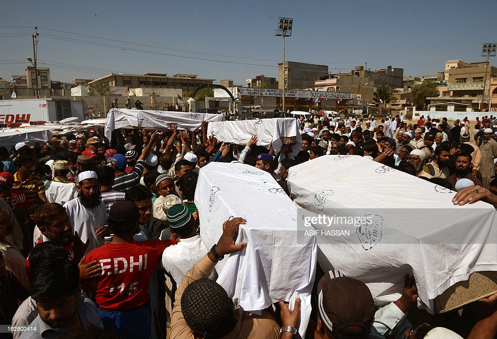 Pakistani mourners carry coffins, released by authorities after months of forensics investigations following their deaths in a garment factory fire in September last year, during a funeral in Karachi on February 24, 2013. Pakistani police have moved to drop murder charges against the owners of a garment factory where 289 workers were killed in a fire in September 2012, the mens' lawyer said February 11. AFP PHOTO/Asif HASSAN