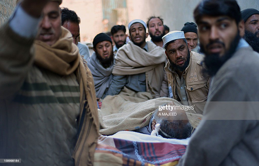 Pakistani mourners carry the dead body of an Al-Khidmat worker after unknown armed men shot him and another man at a market in Charsadda on January 5, 2012. At least two workers of a religious welfare organisation Al-Khidmat education foundation were shot dead by armed men when they travelling in a market. AFP PHOTO/ A MAJEED