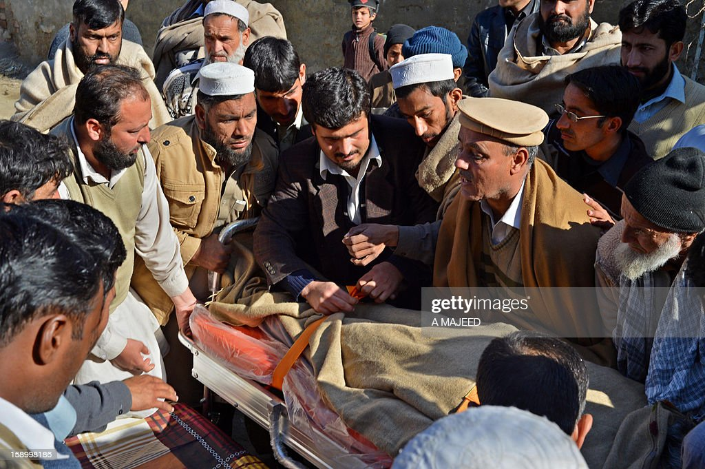 Pakistani mourners carry the dead body of an Al-Khidmat worker after unknown armed men shot him and another man at a market in Charsadda on January 5, 2012. At least two workers of a religious welfare organisation Al-Khidmat education foundation were shot dead by armed men when they travelling in a market.