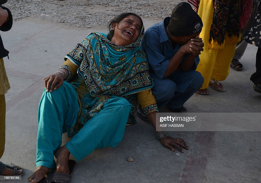 Pakistani mourners cry over the death of their relatives after an explosion on a passenger bus, outside a hospital, in Karachi on December 29, 2012. At least four people were killed and dozen wounded when a loud explosion ripped apart a passenger bus outside the railway station in the port city of Karachi, the nature of the explosion could not be ascertained. AFP PHOTO/ Asif HASSAN