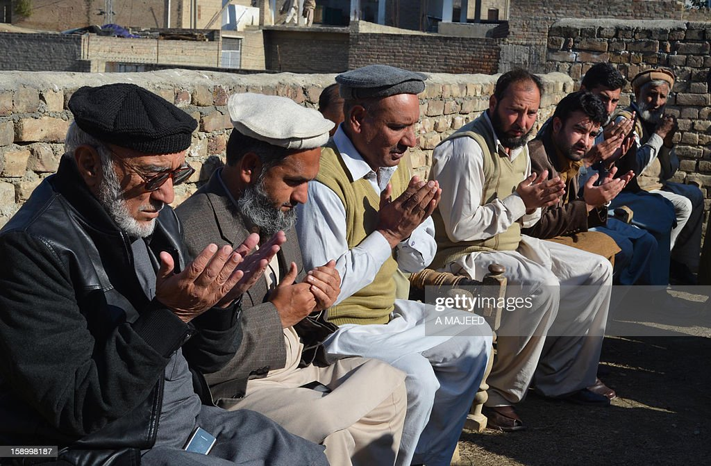 Pakistani mourners pray for an Al-Khidmat worker killed after unknown armed men shot him and another man at a market in Charsadda on January 5, 2012. At least two workers of a religious welfare organisation Al-Khidmat education foundation were shot dead by armed men when they travelling in a market.