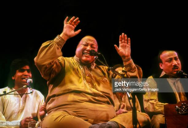 Pakistani musician Nusrat Fateh Ali Khan sings Qawwali devotional Sufi music with his group Party at a World Music Institute concert at Town Hall New...