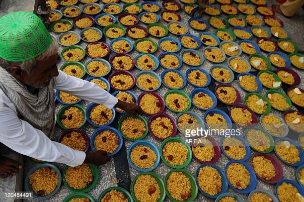 A Pakistani Muslim arranges bowls of food before Iftar the breaking of the fast during the Muslim holy month of Ramadan in Lahore on August 6 2011...