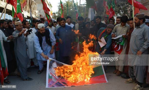 Pakistani Muslim burn the flag of Myanmar flag with a picture of Myanmar's civilian leader and Nobel peace laureate during a protest against the...