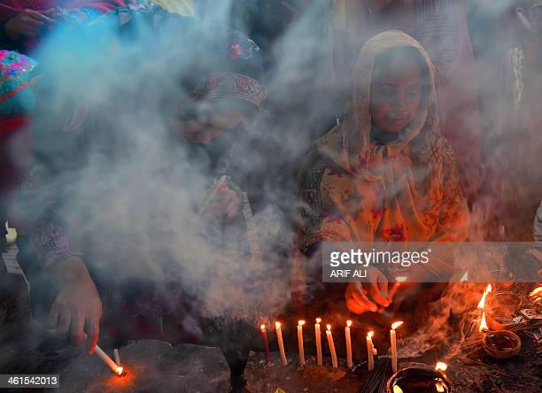Pakistani Muslim devotees light candles and oil lamps at the shrine of the Sufi saint Mian Mir Sahib during a festival to mark his 369th death...