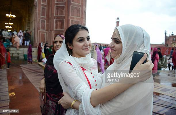 Pakistani Muslim devotees offer Eid greetings after prayers on the first day of the Eid alFitr festival at Badshahi Masjid in Lahore on July 29 2014...