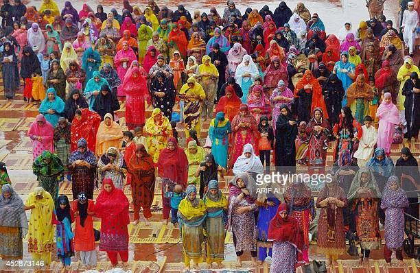 Pakistani Muslim devotees offer Eid prayers on the first day of the Eid alFitr festival at Badshahi Masjid in Lahore on July 29 2014 Muslims around...