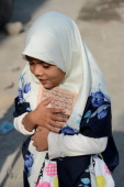 A Pakistani Muslim girl holds the holy book Koran as she arrives to attend seminary in Rawalpindi on November 4 2012 AFP PHOTO/ Farooq NAEEM