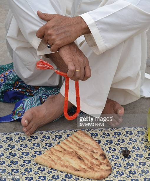 A Pakistani Muslim man counts prayer beads as he waits to break his fast during the holy fasting month of Ramadan in Quetta on July 2 2014 The...