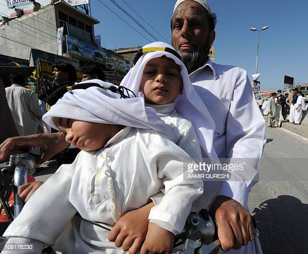 A Pakistani Muslim man drives a motorbike along with children at a march during celebrations marking EideMiladunNabi the birth of Islam's Prophet...