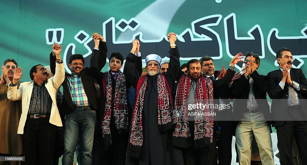 Pakistani Muslim scholar Tahir-ul Qadri (C) joins hands with the leaders of the Muttahida Qaumi Movement (MQM) political party, during a public rally in Karachi on January 1, 2013. A motorcycle bomb exploded Tuesday near the venue of a major political rally in Pakistan's largest city Karachi, killing two people and injuring 25 others, police said. The bombing appeared to be targeted at buses carrying supporters of the city's dominant political party, the Muttahida Qaumi Movement (MQM), which organised the rally attended by thousands of people.