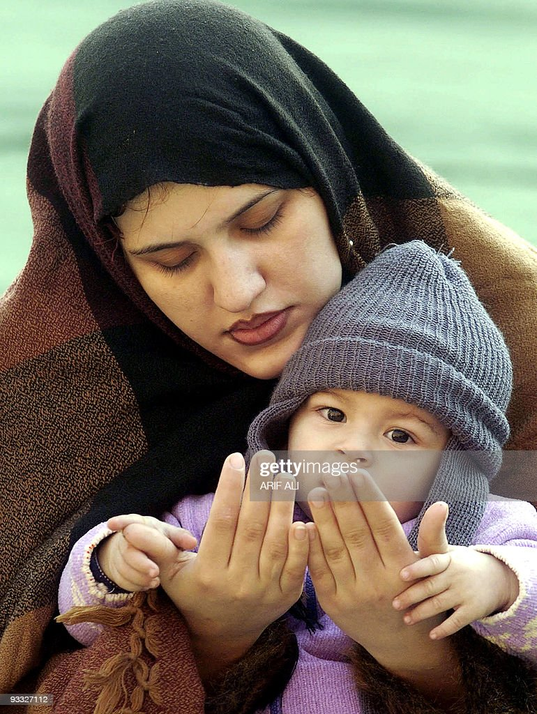 A Pakistani Muslim Woman Offers Prayer As She Holds Her Child At The  Historical Badshahi Mosque