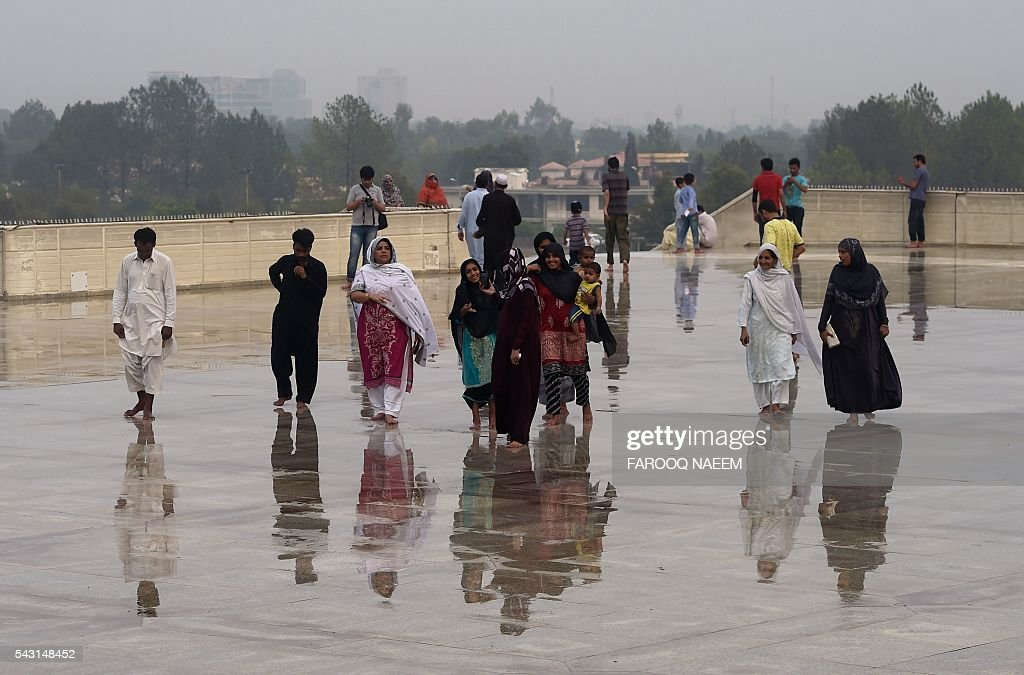 Pakistani Muslims arrive at the Grand Faisal mosque after rains in Islamabad on June 26, 2016. Muslims throughout the world are marking the month of Ramadan, the holiest month in the Islamic calendar during which devotees fast from dawn till dusk. / AFP / FAROOQ