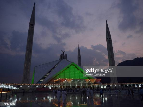 Pakistani Muslims arrive for prayers at the illuminated Faisal Mosque in Islamabad on August 5 2013 during Lailat alQader also known as the Night of...