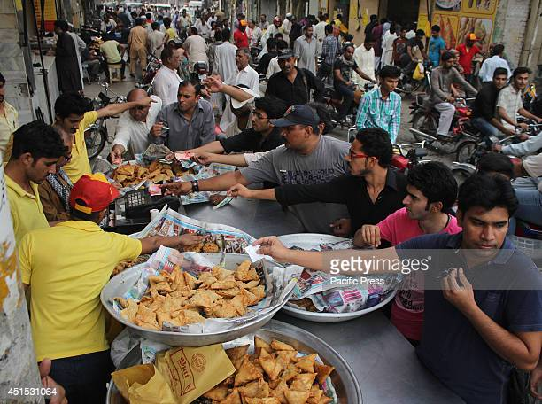 Pakistani Muslims buy fries and samosas from a shop after their fast after sunset in Lahore The fasting month of Ramadan is sacred for the world's...