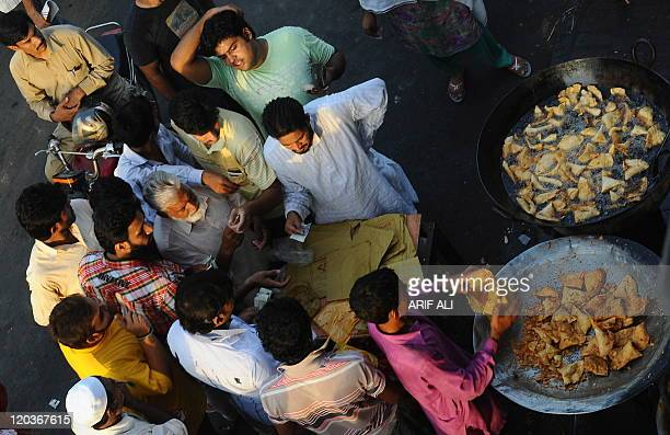 Pakistani Muslims buy samosas from a street vendor prior to breaking the first day of fasting during the holy month of Ramadan in Lahore on August 2...