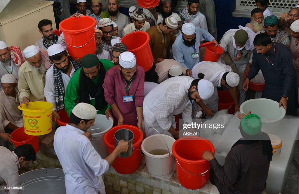 Pakistani Muslims distribute drink on the start of Itikaf in a mosque in Lahore on June 26, 2016. Itikaf is a spiritual retreat in a mosque for men, usually held during the last 10 days of Ramadan and during which Muslims spend the evening and night in the mosque devoting their time to solitary prayers and reading the Koran. / AFP / ARIF ALI