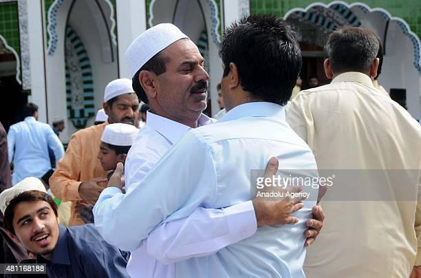 Pakistani Muslims exchange Eid greetings after performing Eid alFitr Prayer at DarbareAlia Eidgah Sharif in Rawalpindi Pakistan on July 18 2015...