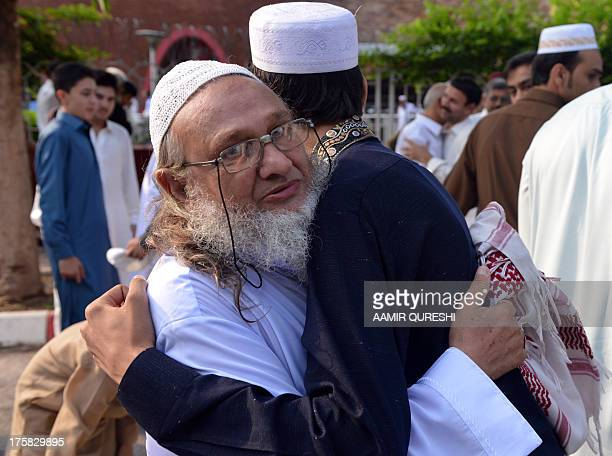 Pakistani Muslims exchange greetings after offering Eid alFitr prayers during the first day of their religious festival in Islamabad on August 9 2013...