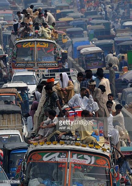 Pakistani Muslims travel on overloaded buses as they head to their hometowns ahead of the Muslim festivities of Eid alFitr in Lahore on August 7 2013...