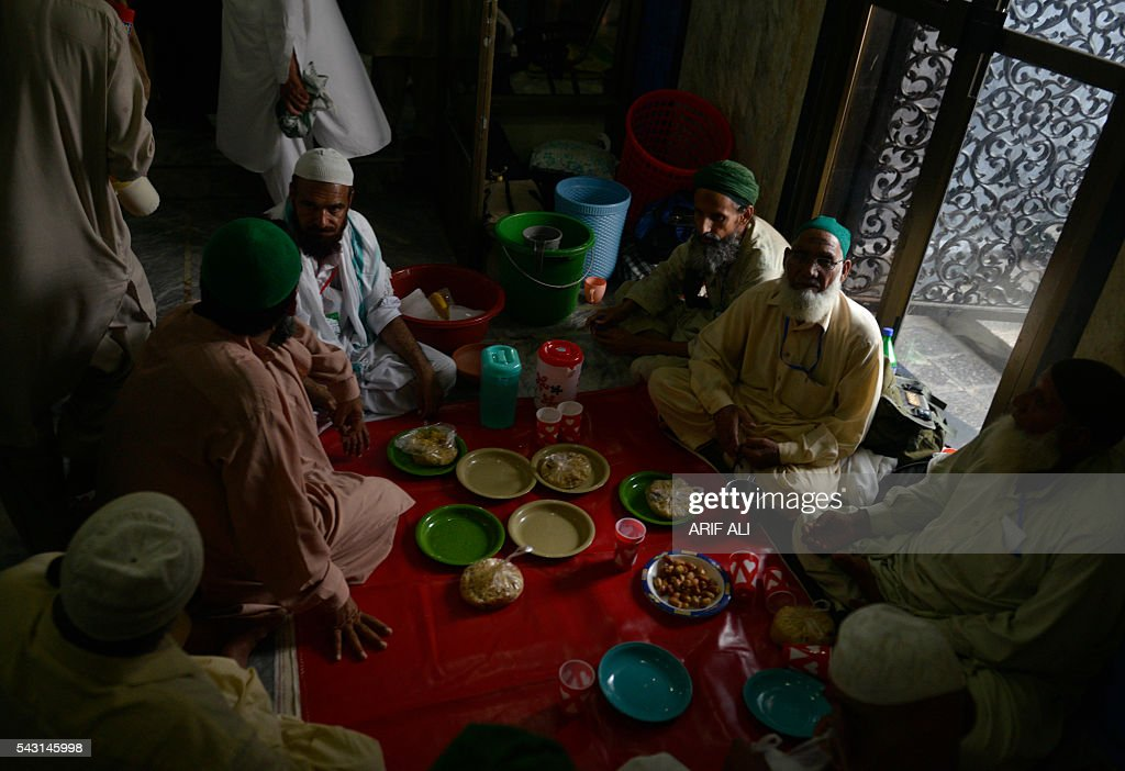 Pakistani Muslims wait to break their fast on the start of Itikaf in a mosque in Lahore on June 26, 2016. Itikaf is a spiritual retreat in a mosque for men, usually held during the last 10 days of Ramadan and during which Muslims spend the evening and night in the mosque devoting their time to solitary prayers and reading the Koran. / AFP / ARIF ALI