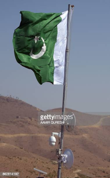 Pakistani national flag waves with electronic surveillance equipment near a newly fenced border fencing along Afghan border at Kitton Orchard Post in...