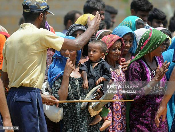 A Pakistani navy soldier controls floodaffected victims gather for relief good at a navy distribution point in a makeshift camp in Thatta district on...