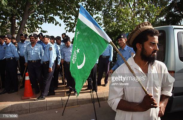 Pakistani opposition party member stands in front of a line of policemen after a supreme court decision is announced in favor of Pakistani President...