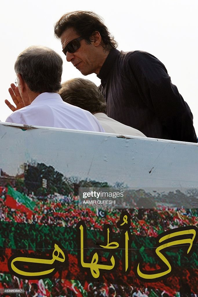 Pakistani opposition politician Imran Khan (R) heads a party core committee meeting on a stage held at an anti-government protest site in front of the Parliament in Islamabad on August 22, 2014. Pakistani opposition politician Imran Khan called August 21 off talks with the government aimed at ending protests seeking the fall of the prime minister, which have unnerved the nuclear-armed nation. Khan and populist cleric Tahir-ul-Qadri have led followers protesting outside parliament for the past two days demanding Prime Minister Nawaz Sharif quit. AFP PHOTO/ Aamir QURESHI