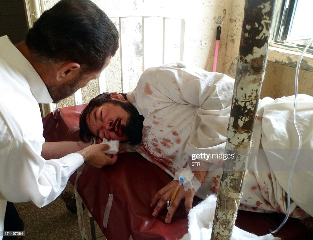 A Pakistani paramedic treats an injured blast victim at a hospital in Parachinar, the main town of Kurram tribal district on July 26, 2013, following twin bomb explosions. At least 25 people were killed and more than 100 others wounded when twin explosions ripped through a market in the northwest Pakistan, administration and hospital officials said.