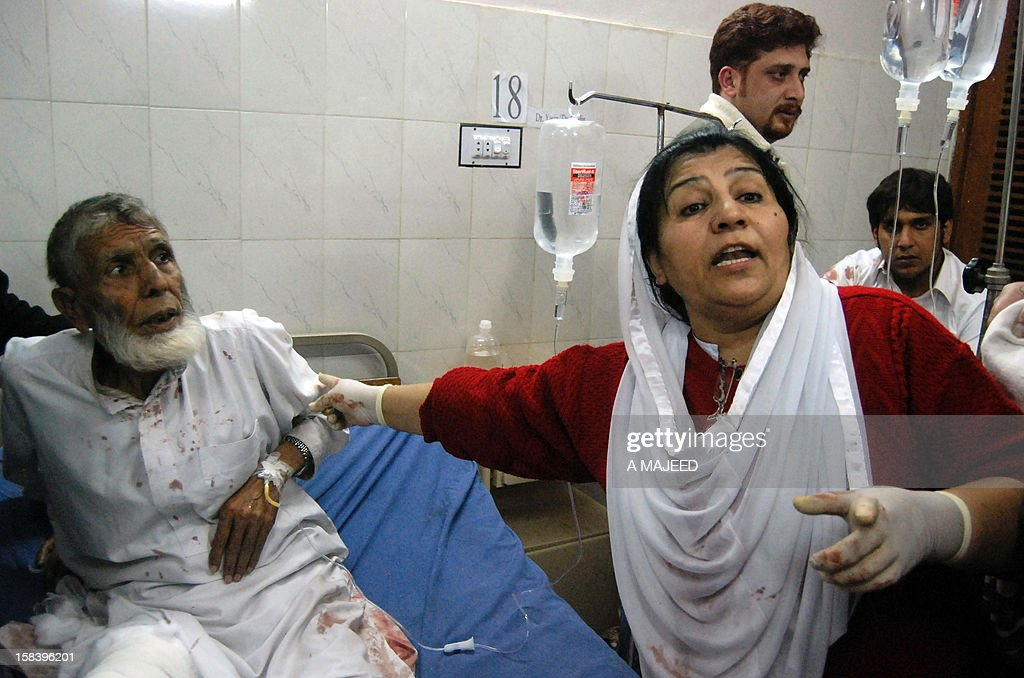 A Pakistani paramedic treats an injured man after a rocket attack on an airport in Peshawar on December 15, 2012. Militants fired rockets into the airport of Pakistan's northwestern city Peshawar late on Saturday, killing four people, wounding dozens more and forcing the airport to close, officials said. AFP PHOTO/A MAJEED