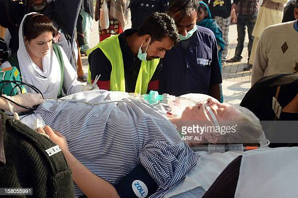 Pakistani paramedics transport injured Christian charity worker Bargetta Almby on a stretcher from a hospital to an air ambulance in Lahore on...