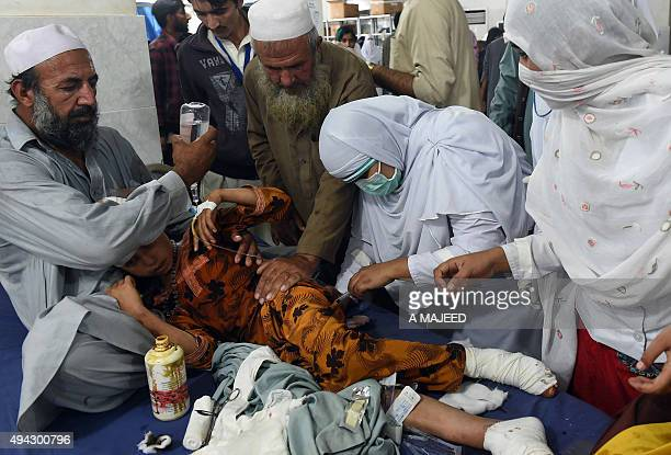 Pakistani paramedics treat a girl injured in an earthquake at a hospital in Peshawar on October 26 2015 At least 17 people including eight children...