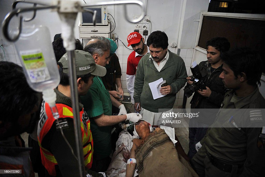 Pakistani paramedics treat an injured bomb blast victim at a hospital in Peshawar on February 1, 2013, after an explosion outside a Shiite Muslim mosque in Hangu. A suicide bomber targeted a Shiite Muslim mosque in northwest Pakistan on Friday, killing 21 people and wounding up to 50 as worshippers poured out of weekly prayers, officials said. AFP PHOTO/A MAJEED