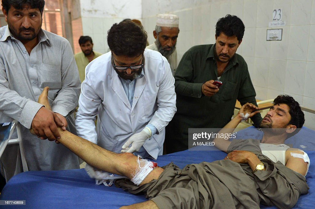 Pakistani paramedics treat an injured man following a bomb blast in Peshawar on April 29, 2013. A suicide bomber killed at least eight people and wounded 45 others when he rammed his motorcycle into a bus in Pakistan's northwestern city of Peshawar on Monday, police said. AFP PHOTO/A MAJEED