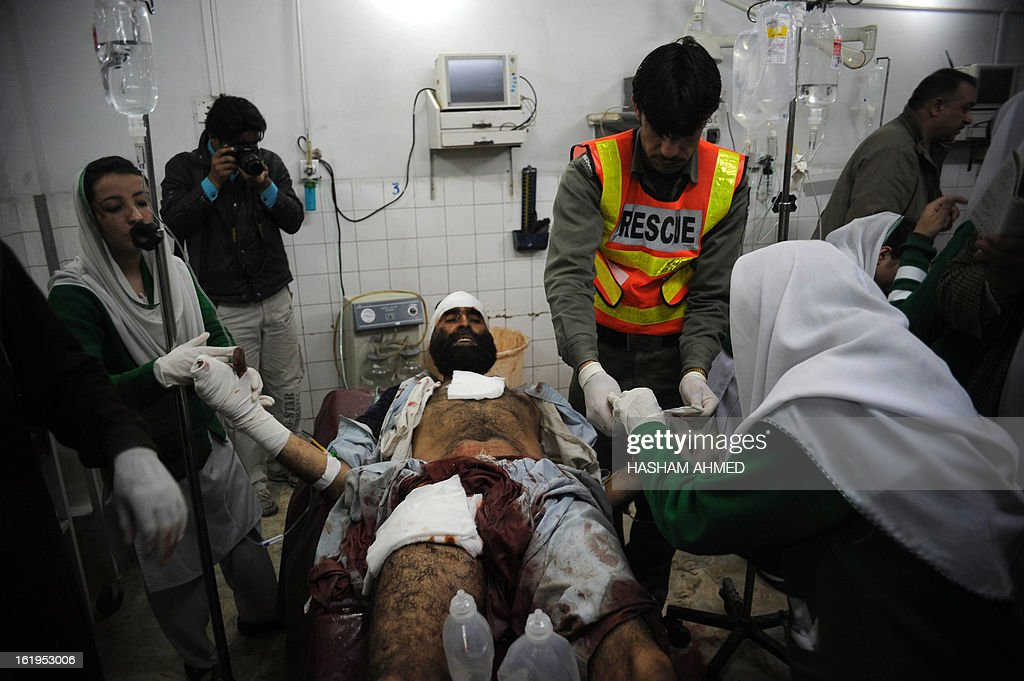 Pakistani paramedics treat an injured victim after the militants' attack on the office of the top political official of Khyber tribal region in Peshawar on February 18, 2013. Militants including a suicide bomber attacked the office of a senior official in Pakistan's northwestern city of Peshawar on Monday, killing five people, officials said. AFP HOTO/Hasham AHMED