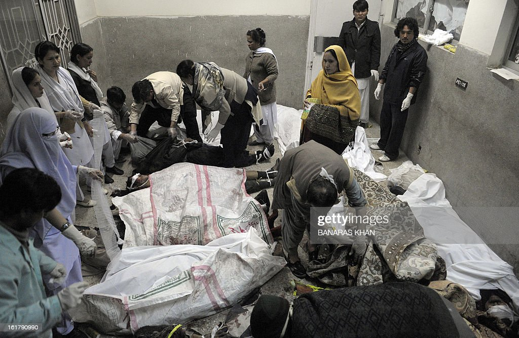 Pakistani paramedics work over the dead bodies of bomb blast victims at a hospital in Quetta on February 16, 2013. A remote-controlled bomb targeting Shiite Muslims killed 47 people including women and children and wounded more than 200 in Pakistan's insurgency-hit southwest on Saturday, police and officials said. AFP PHOTO/Banaras KHAN